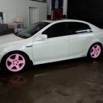 Car with the pink to orange glow in the dark wheels in the light.